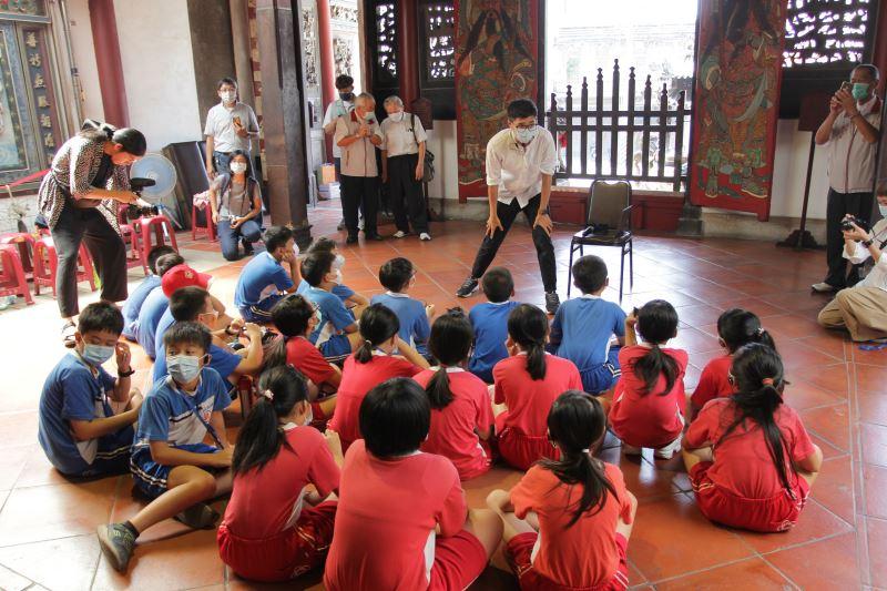 磚木取夥故事劇場在興濟宮向公園國小的學童說繪本《老房子》故事