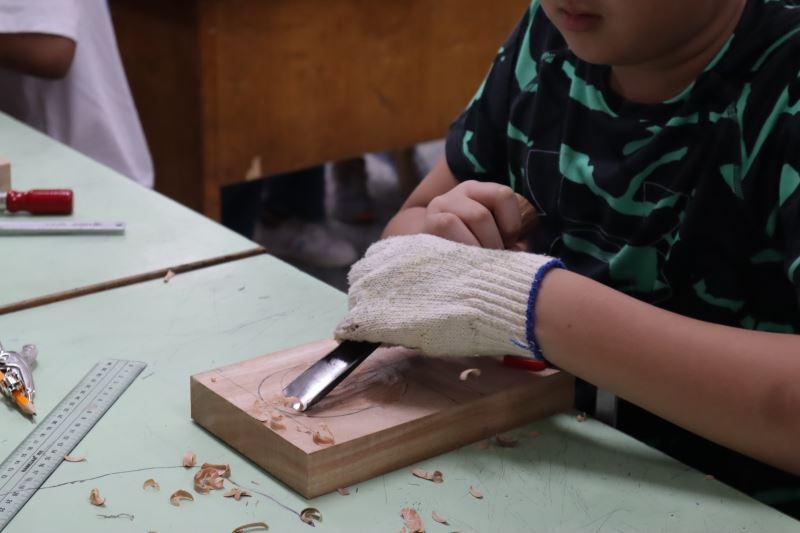 04-學生嘗試用雕刻刀在木頭上挖出凹槽。