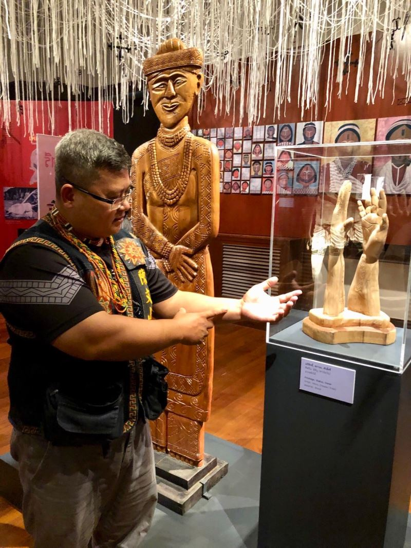 Figure 3. Paiwan tattooist Cudjuy Maljugau demonstrated the tattooing process in the exhibition.