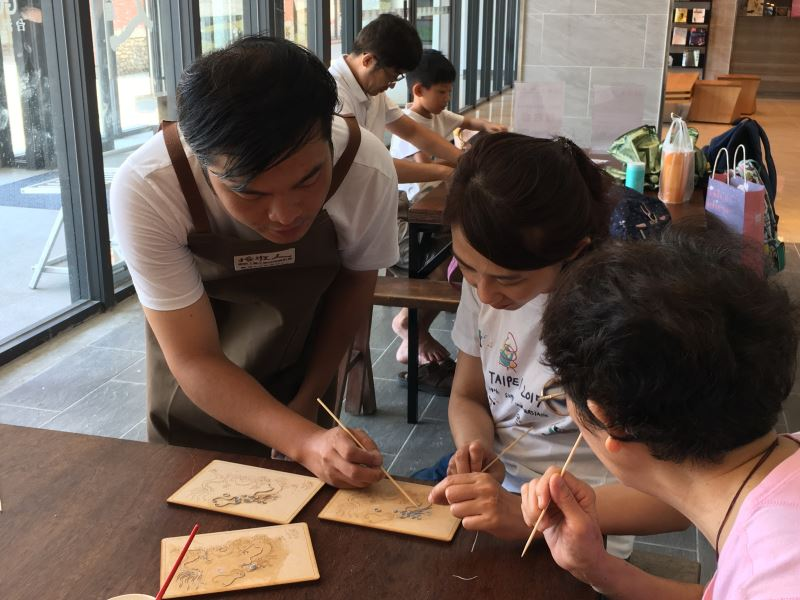 粧佛工藝師陳宗蔚教導遊客如何盤漆線