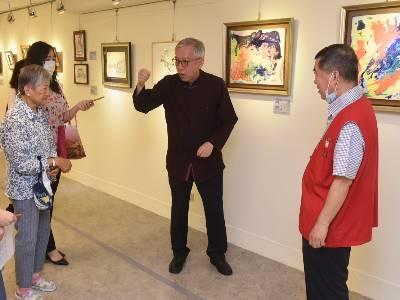 梁永斐館長於員工志工藝文展說明流體畫的創作流程