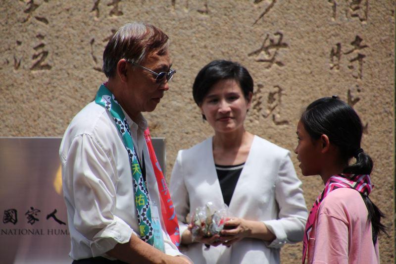 政治受難者前輩陳欽生(左)將人權彩飄親手掛在綠島公館國小學童身上