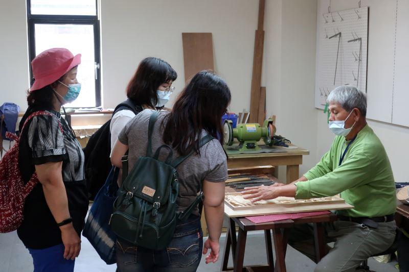 傳統木雕工藝師吳適為向民眾介紹傳統圖騰中的寓意故事。