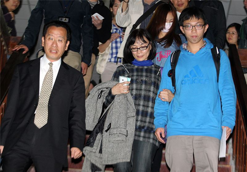 Yang Tsui (center), Wei Yang (right), and attorney Gu Lixiong (left) leaving court, March 25, 2014. (Source: Central News Agency)