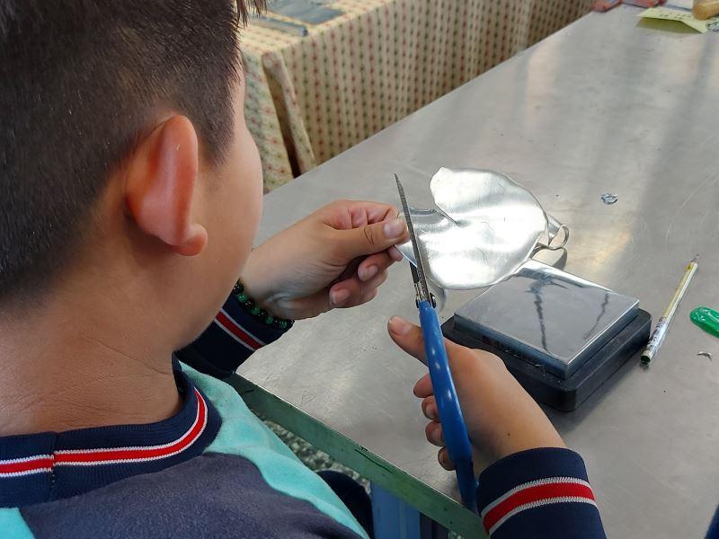 09-同學使用剪刀剪裁錫盤的形狀。