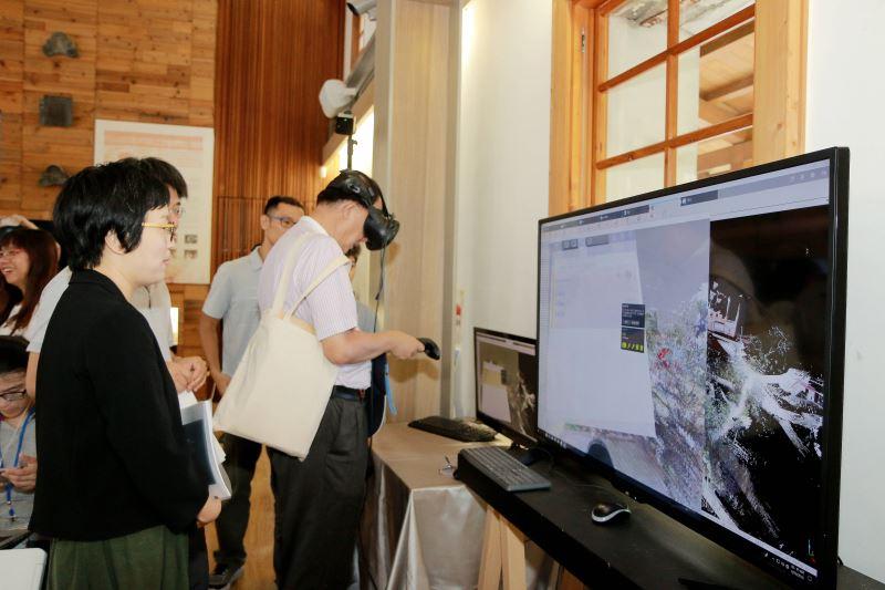 文化部文化資產局長施國隆(右一)正在操作臺灣數位模型資料庫。