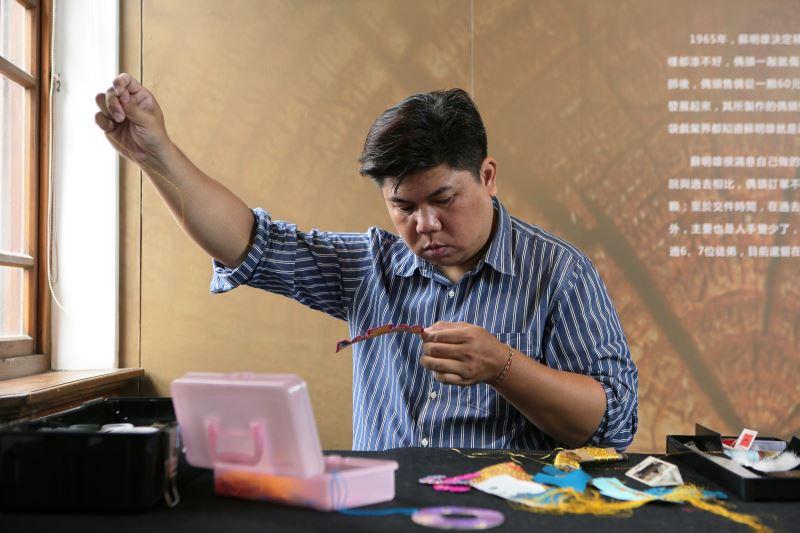 倪紳發堅持保留傳統精巧細膩的手做工法,一針一線手工縫製布袋戲偶服飾。