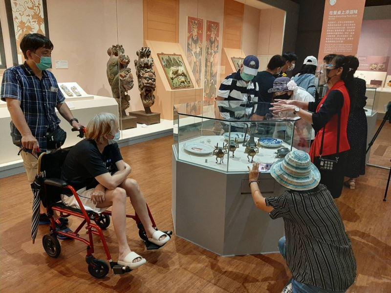 民眾專心聆聽導覽員介紹在飲食器皿中會出現的傳藝動物及當中的涵義。