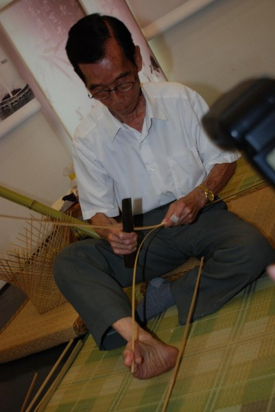 Using his right toes to steady the graft, Huang can control the angle and thickness of the bamboo strips.