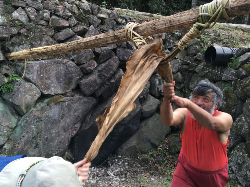鞣皮須兩人一組合作,藉由反覆拉扯黃藤,讓皮革慢慢軟化;圖為鄒族獵人浦少光鞣皮的過程。