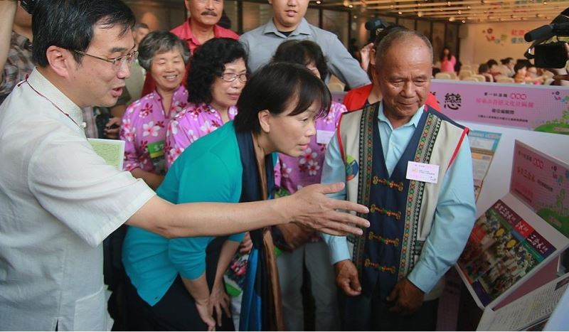 At the April 11 awards ceremony, Culture Minister Lung Ying-tai (center, in emerald) flipped through the pages of the 32 winning papers and talked with the residents who took part in the reporting.