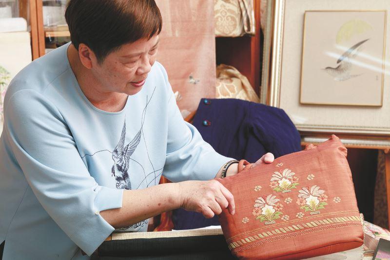 劉千韶拿起自己刺繡裝飾的包包,珍惜之情不言而喻。