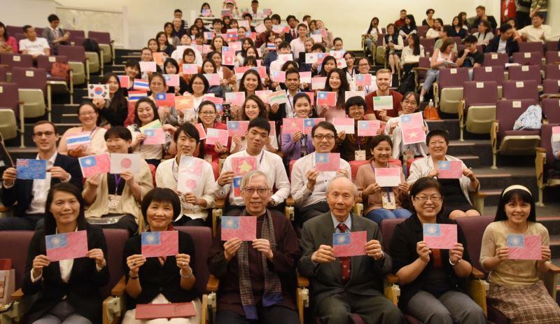 「2019年外籍學生華語文演講比賽」參賽者手繪母國及中華民國國旗與梁永斐館長(前排左3)及五位評審委員合影