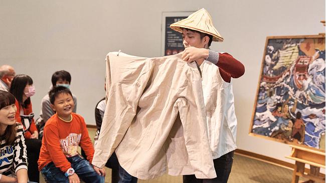 迷你劇場戲劇導覽活動照片,導覽人員正帶著斗笠,演戲給小朋友看