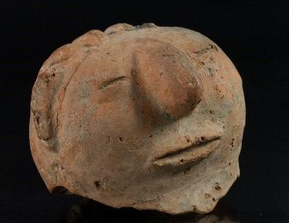 A face-shaped ceramic pot.