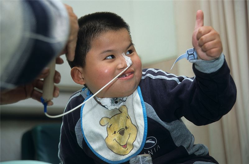 "Since birth, he has had to ""ingest"" food (rather than ""eating"" it) with a nasal tube—hence his nickname ""Elephant Boy."" Shan Shan is an eight-year-old girl with severe cerebral palsy, raised by her elderly grandmother."