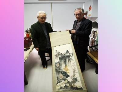 林章湖教授(左)向國父紀念館梁永斐館長介紹其14歲臨摹張大千〈秋壑鳴泉〉圖作品