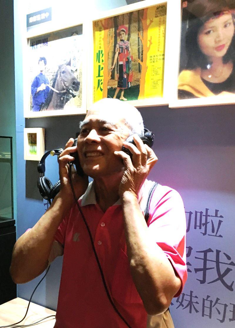 長輩開心的帶著耳機聆聽音樂並跟著吟唱