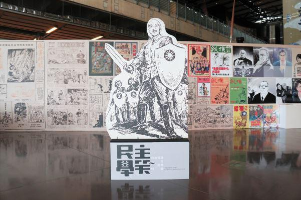 展櫃背後牆面由日本時期至當代的政治漫畫串連而成,其中蔣中正漫畫形象出自民國39年《中央日報漫畫半週刊》。