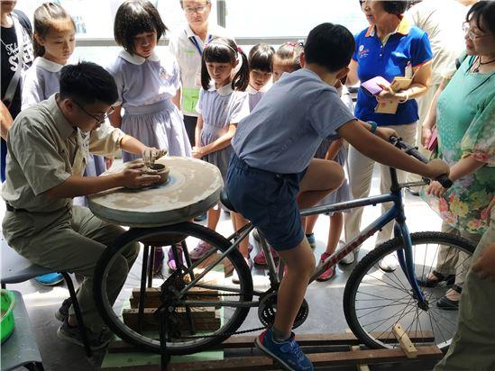 小朋友負責踩踏南一中學生製作的人力轆轤,由南一中學生示範拉坯