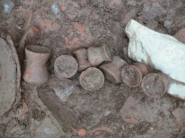 考古現場的照片(請搭配「考古文物3D APP」觀看) 本圖是遺址中剛出土的數個陶罐,它們被排成一列。由於剛出土,陶罐上還沾滿著泥土,附近還有樹根、石頭。 透過「考古3D APP」可以在手機上看到,遺址中還出土了什麼珍貴的文物喔!