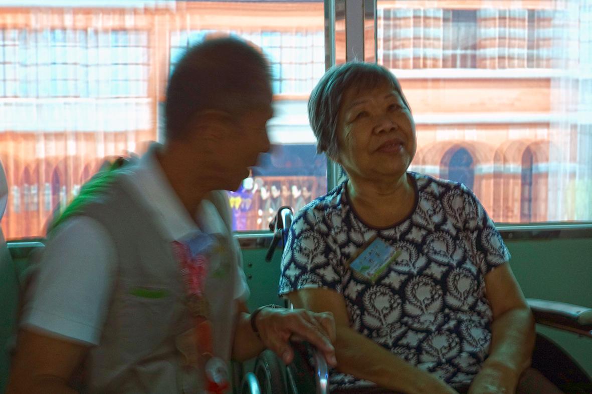 火車劇場導覽活動照片,志工帶著奶奶坐在車廂裡,回憶以前的時光