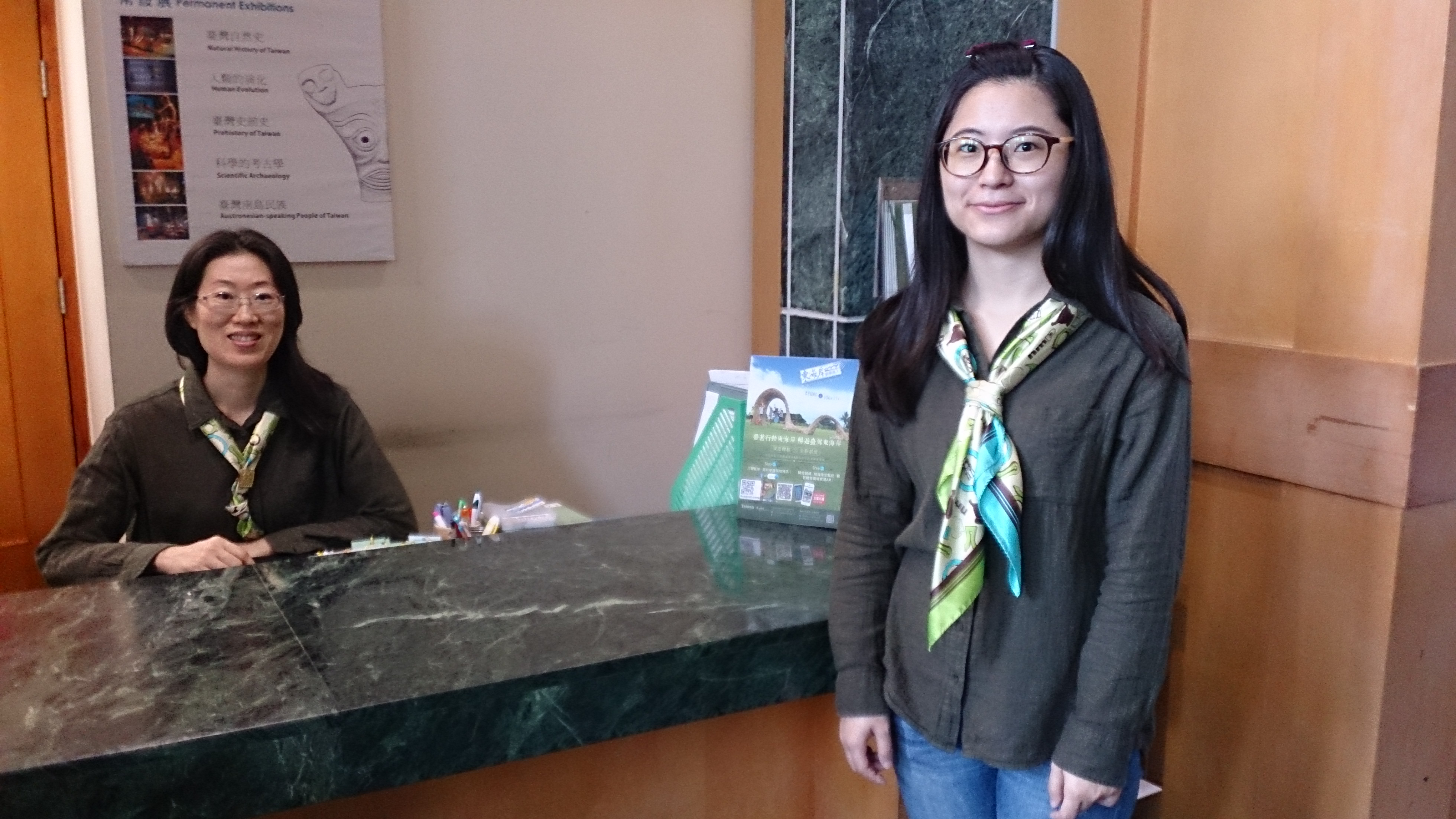康樂本館服務人員服裝照片(冬裝)。服務人員穿著墨綠色襯衫,配戴領巾。